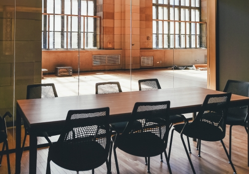 long conference room table and chairs, windows behind the chairs, and what looks like brick walls and a wood floor.